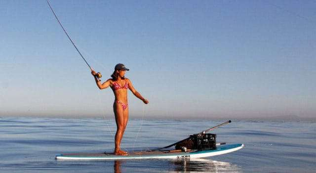 Woman fishing on a paddle board.